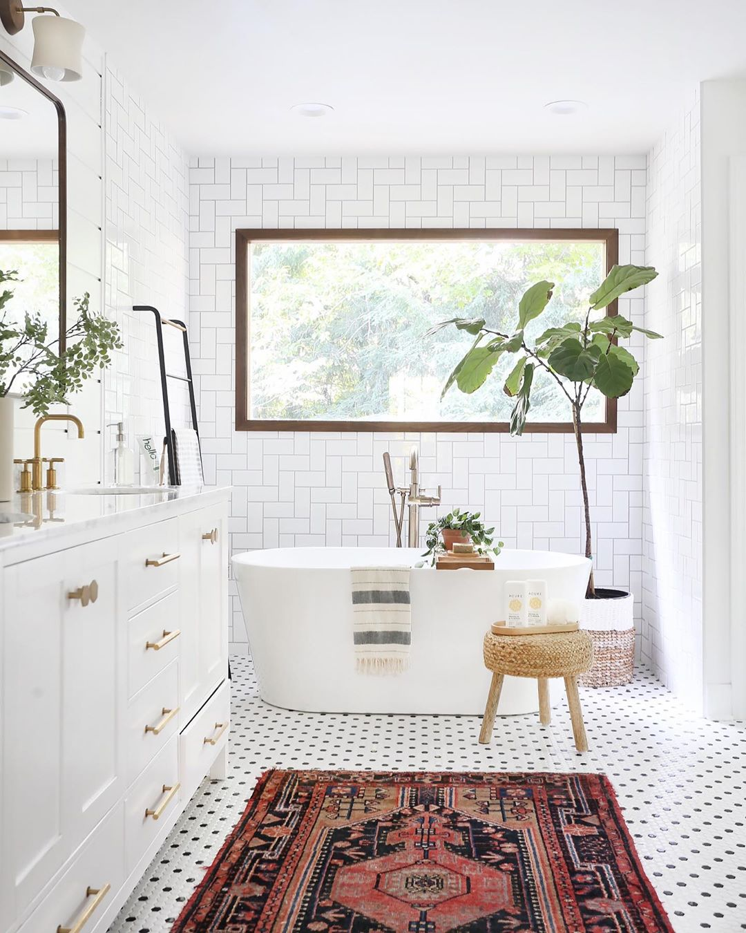 Sunny Circle Studio kept this bathroom full of light with a herringbone tile wall in a stairstep pattern! The tile tub surround was a fun pairing with a classic black and white penny round tile floor and a modern slipper tub to create an airy bathroom that is instantly Pinterest-worthy. The potted plants, woven rattan stool, and vintage bohemian rug add a little eclectic personality to the mix of classic tile patterns!