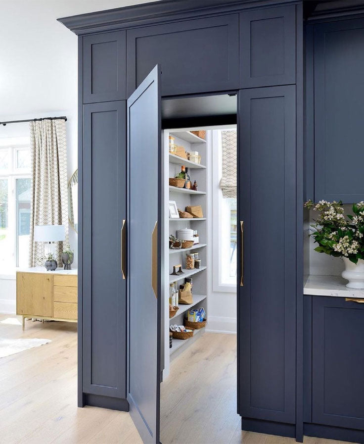 This walk-in pantry design by Michelle Berwick has an effortless flow with the transitional kitchen design, thanks to the plank flooring that seamlessly leads from the living space into the storage area.