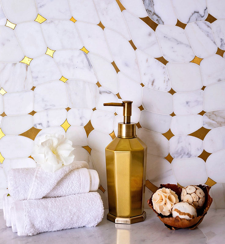 Calacatta Gold and Brass tile in this bathroom vanity backsplash features glowing diamond shapes that match with the copper soap dispenser