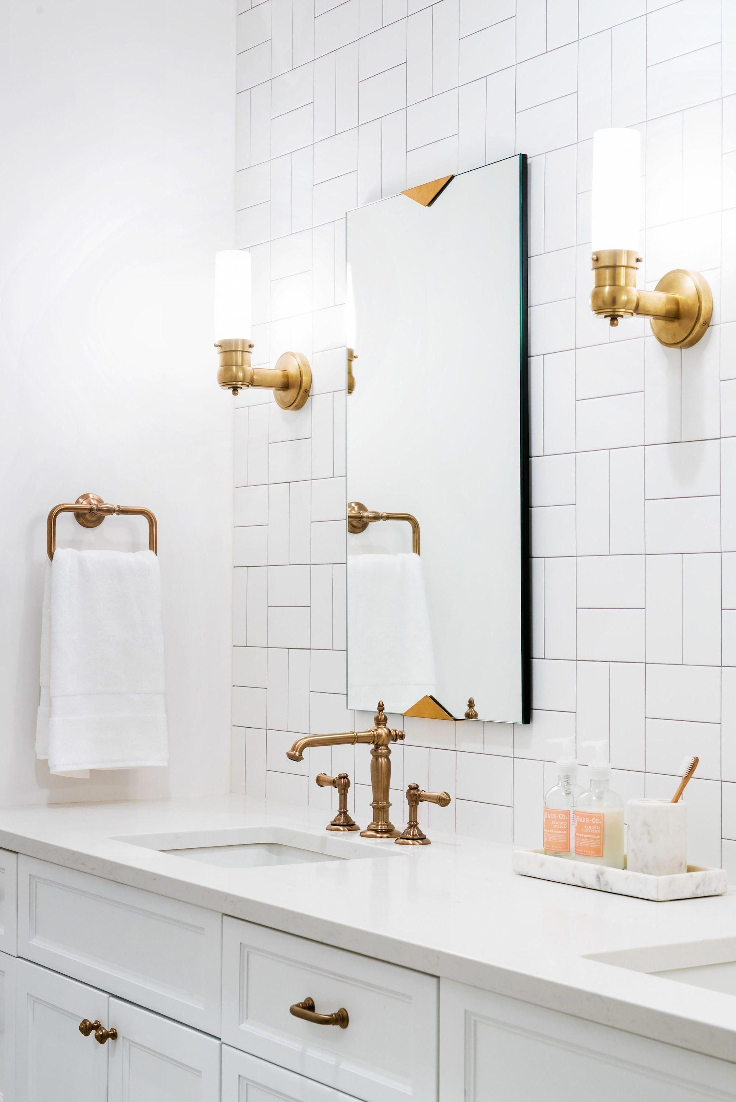 We love this all-white bathroom seen on Jen Talbot design that uses a basketweave or crosshatch pattern with white tile and pairs it with darker contrasting grout for a little bit of contrast! The bronze hardware and marble vanity decor give this minimalist bathroom a beautiful design detail! Love this look? Recreate it with our selection of crisp white subway tiles and a grout like Laticrete Permacolor in Natural Grey!