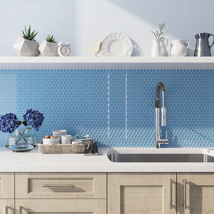 This charming kitchen combines white countertops, natural wood cabinets, and Sky Blue Penny Round Glass Tile for the perfect welcoming home!