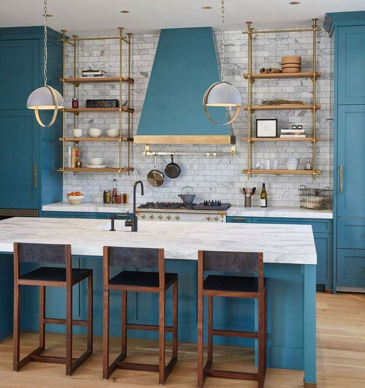 Kitchen with bold blue cabinet paint with brass bistro shelves and marble subway tiles