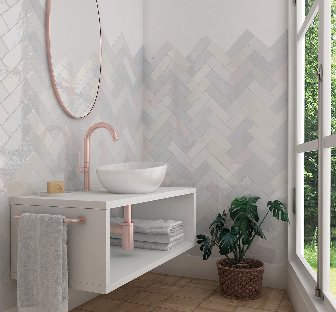 A mix of our La Riviera ceramic tiles gives this modern pastel bathroom with a herringbone subway tile vanity backsplash a subtle rainbow effect - the copper accents make it even more creative!