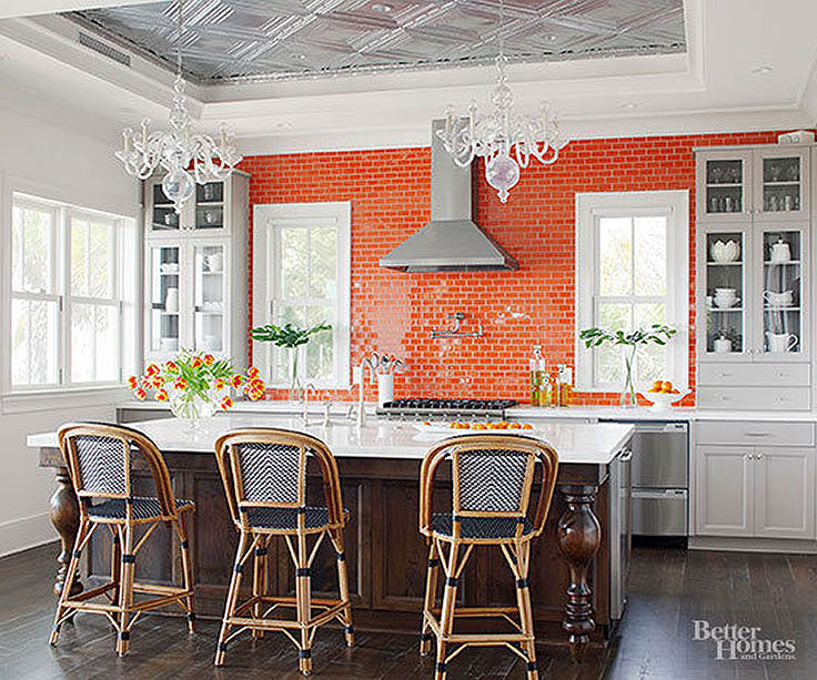 Modern White Kitchen with Bold Orange Tile and Black Chairs