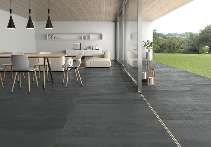 This indoor-outdoor living space embodies the Mid-Century movement with clean linens and large glass walls bringing the outside in - having a transitional flooring material like these steel-look porcelain floor tiles helps to bridge the interior and exterior and create a space that feels as open as possible!