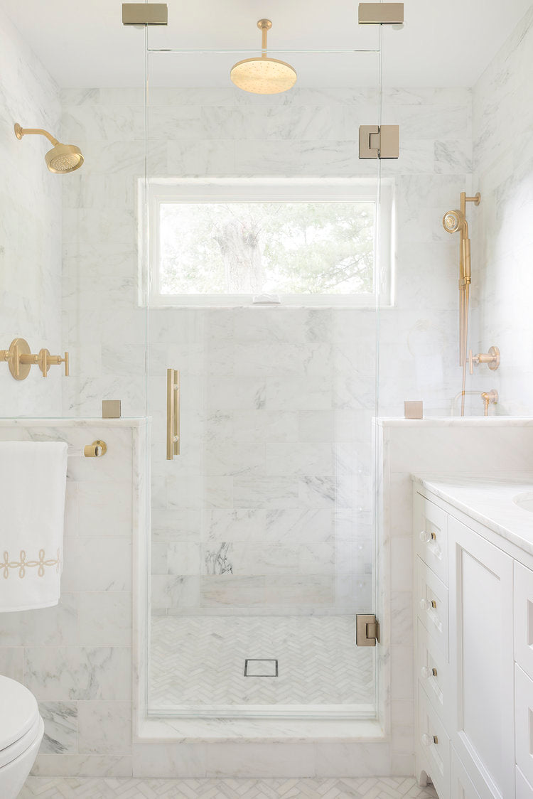 For a chic classic style, imagine stepping into this honed marble stall with brass fixtures - the perfect choice for luxurious, timeless showers!