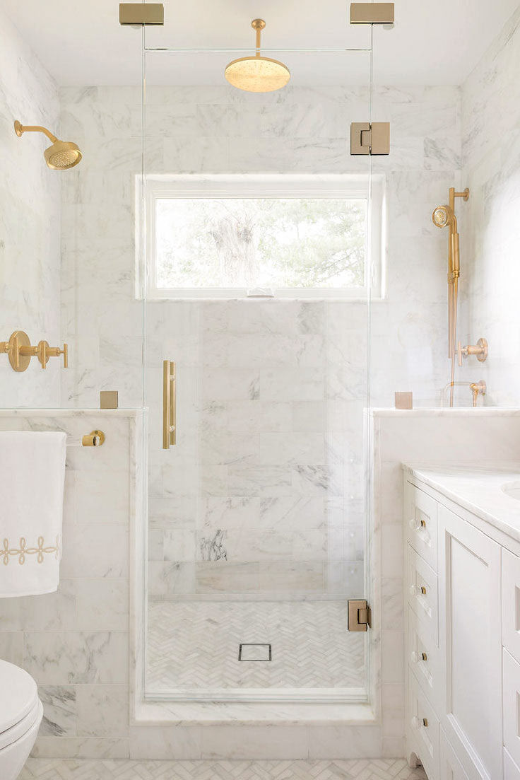 Elegant all-white marble bathroom and walk-in shower with brass shower head and glass door fixtures