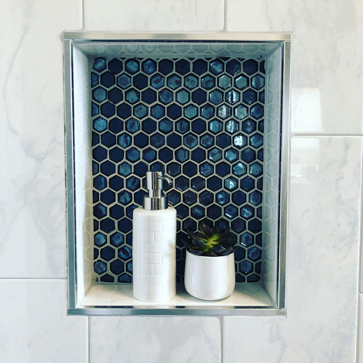 Susie of Feia Construction introduced a jewel tone pop of color to a white shower wall with this blue hexagon mosaic niche