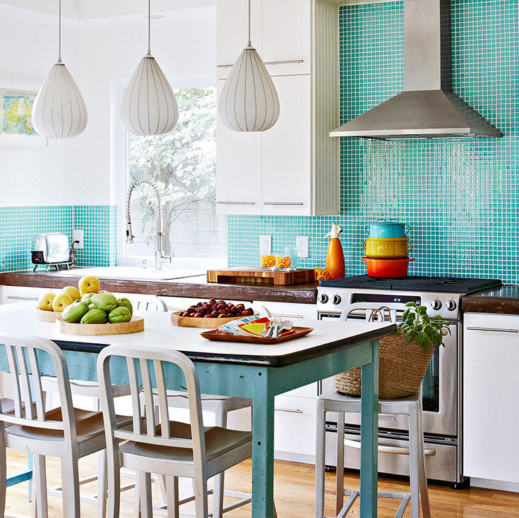 This cheerful kitchen adds a dose of happy color with a teal glass mosaic backsplash while adding in vibrant Le Creuset cookware