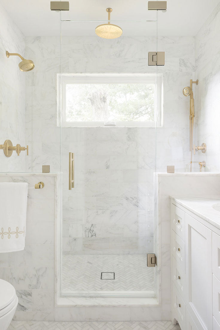 White Calacatta Gold Marble Subway Tile Walk-in Shower with a Herringbone Floor and Gold Fixtures