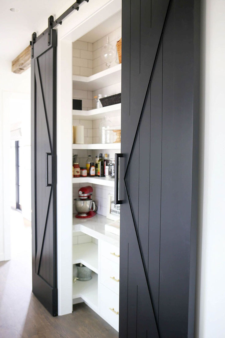 Farmhouse-style sliding barn door hides a prep space and pantry to maximize kitchen storage