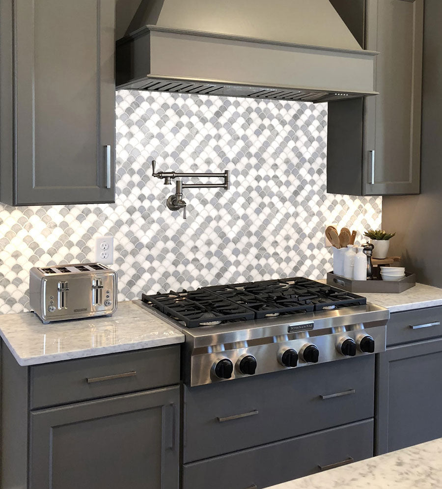 For a small kitchen remodel, go for a mini fish scale tile like the Azul Cielo Thassos and Carrara tile to balance out charcoal gray Shaker cabinets and draw the eye to the main cooking area.