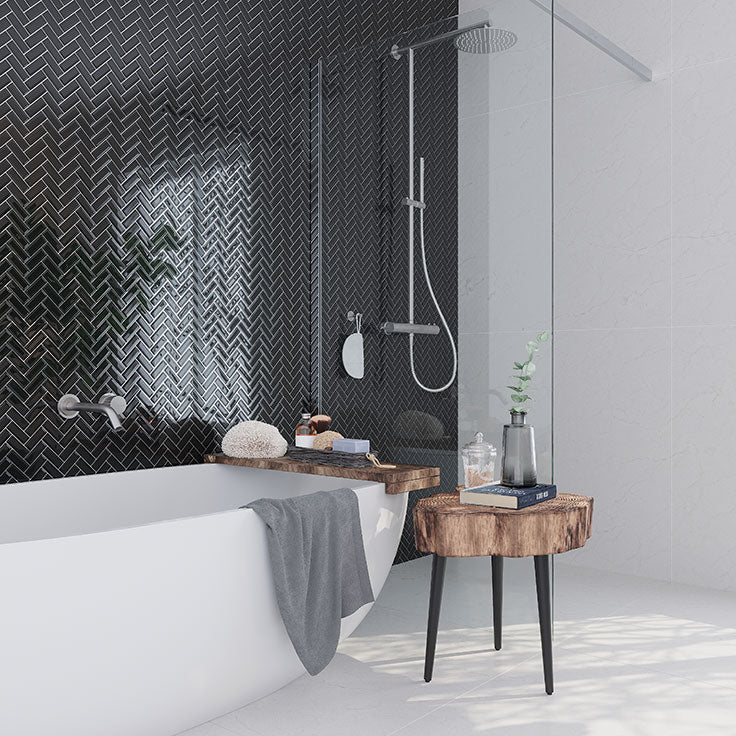 Combine a white free-standing bathtub with Obsidian Black Herringbone Glass Tile for a dramatic contemporary bathroom