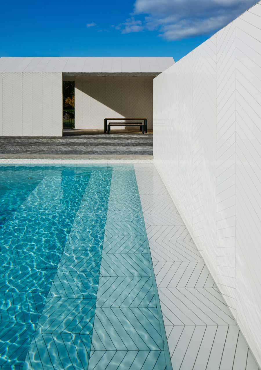 You can create this minimalist and serene pool look seen on Architectural Digest with Ionic Herringbone Sand Porcelain tiles!