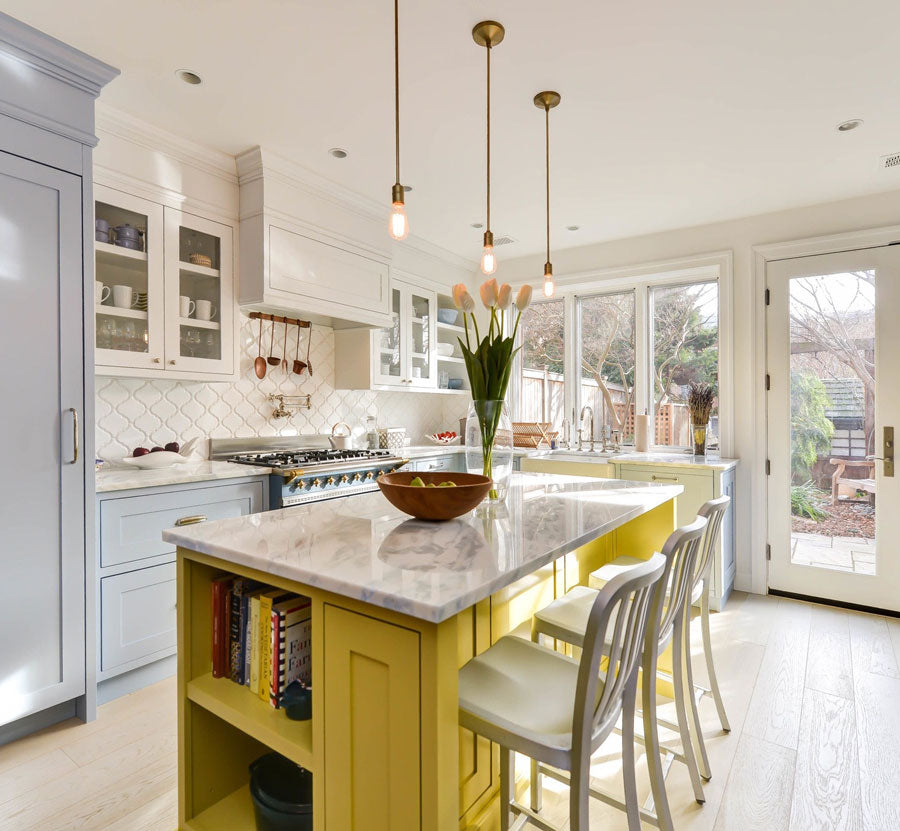This upbeat kitchen in a cozy bed and breakfast rental is so impressive with a cheery yellow island and arabesque mosaic tiles that guests will want to stay home for dinner!
