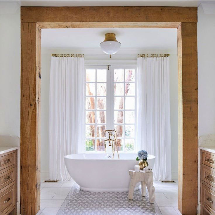Cozy Bath Tub with Wood Framing and an Octagon Patterned Tile Rug