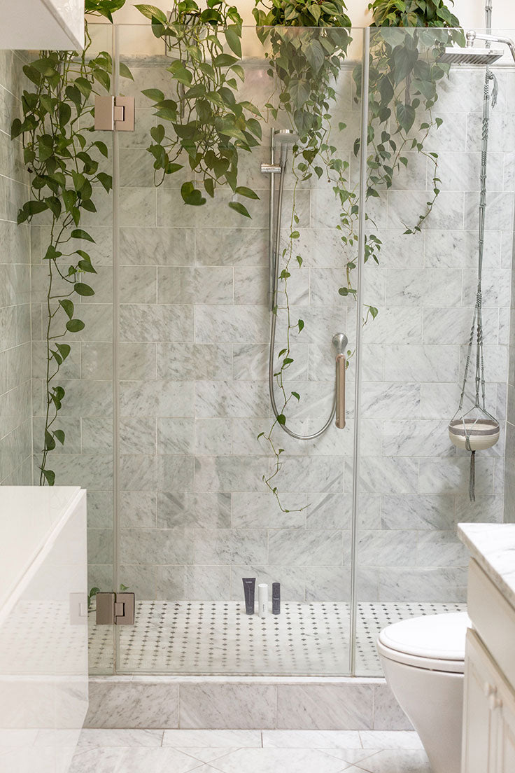 A white and black marble basket weave tile floor paired with marble subway tile shower walls are a gorgeous mix