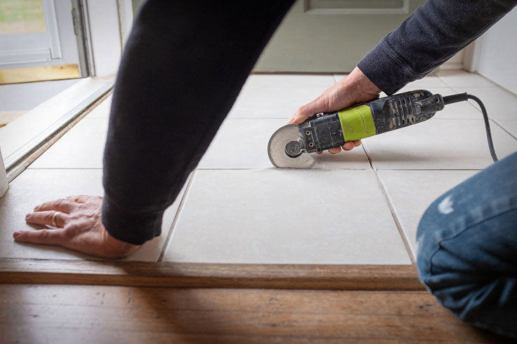 Use a multitool to break up old grout before you regrout