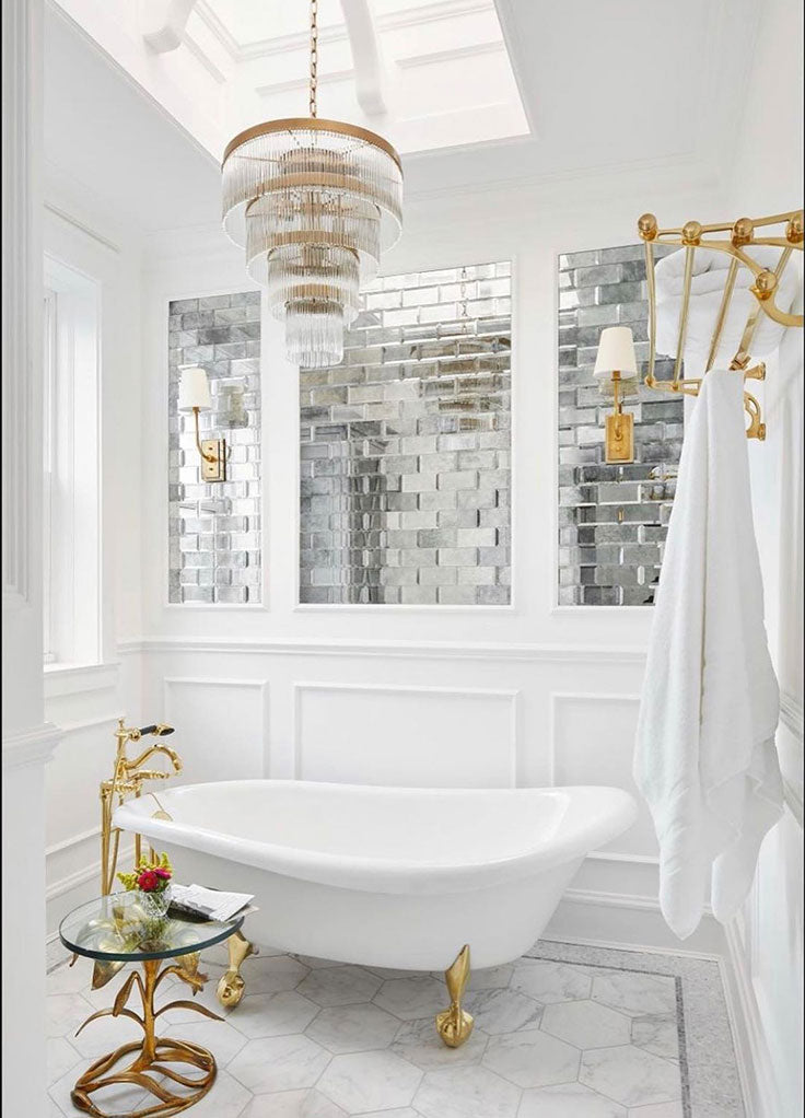 White marble and brass bathroom complements the vintage finish of antique glass mirror tiles