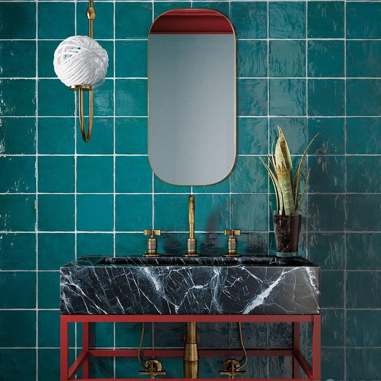 La Riviera Quetzal Ceramic Tile in Jewel Tone Green with a Modern Marble Farm Sink and Gold Bathroom Fixtures