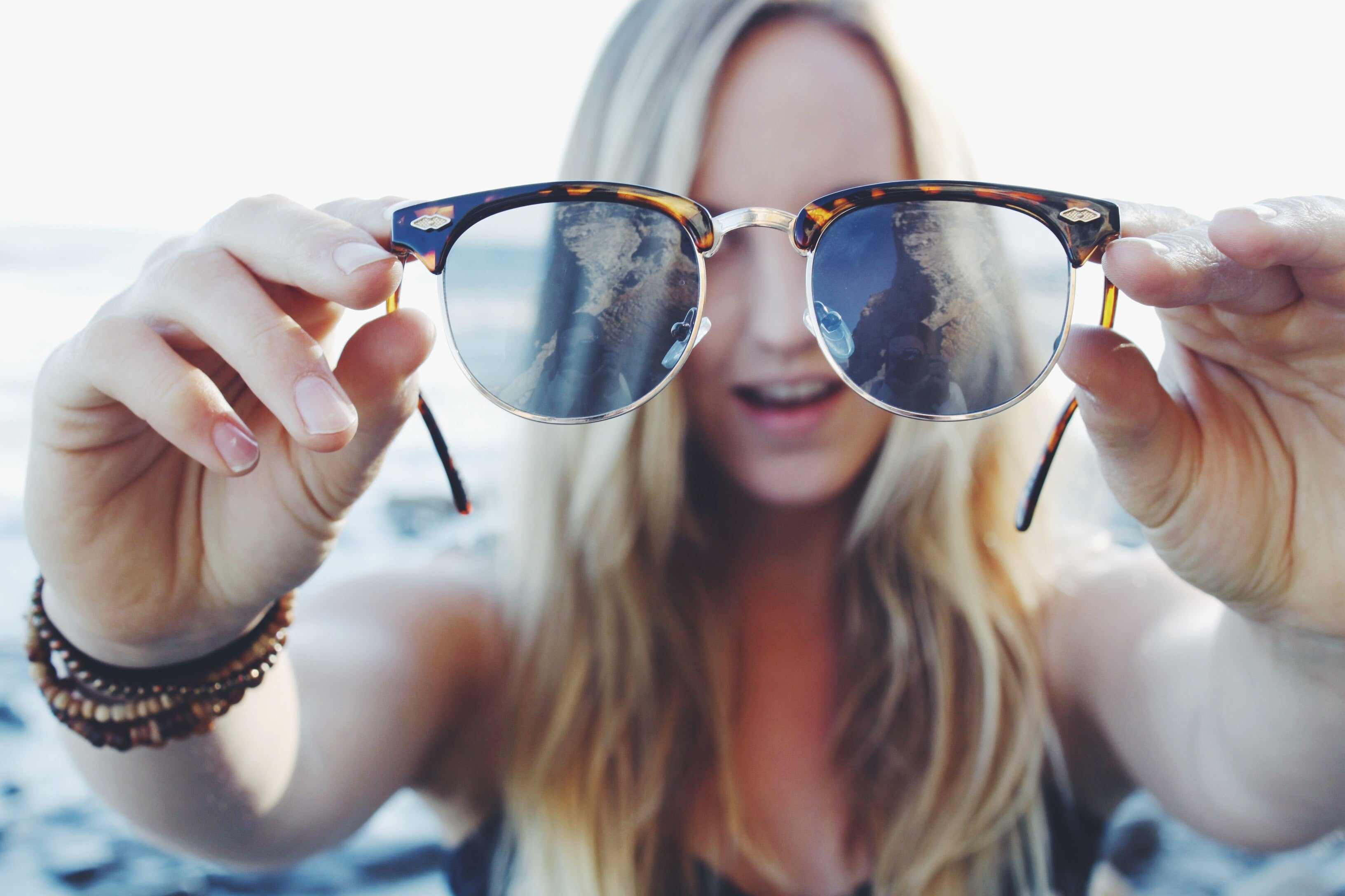low angle picture of girl holding sunglasses