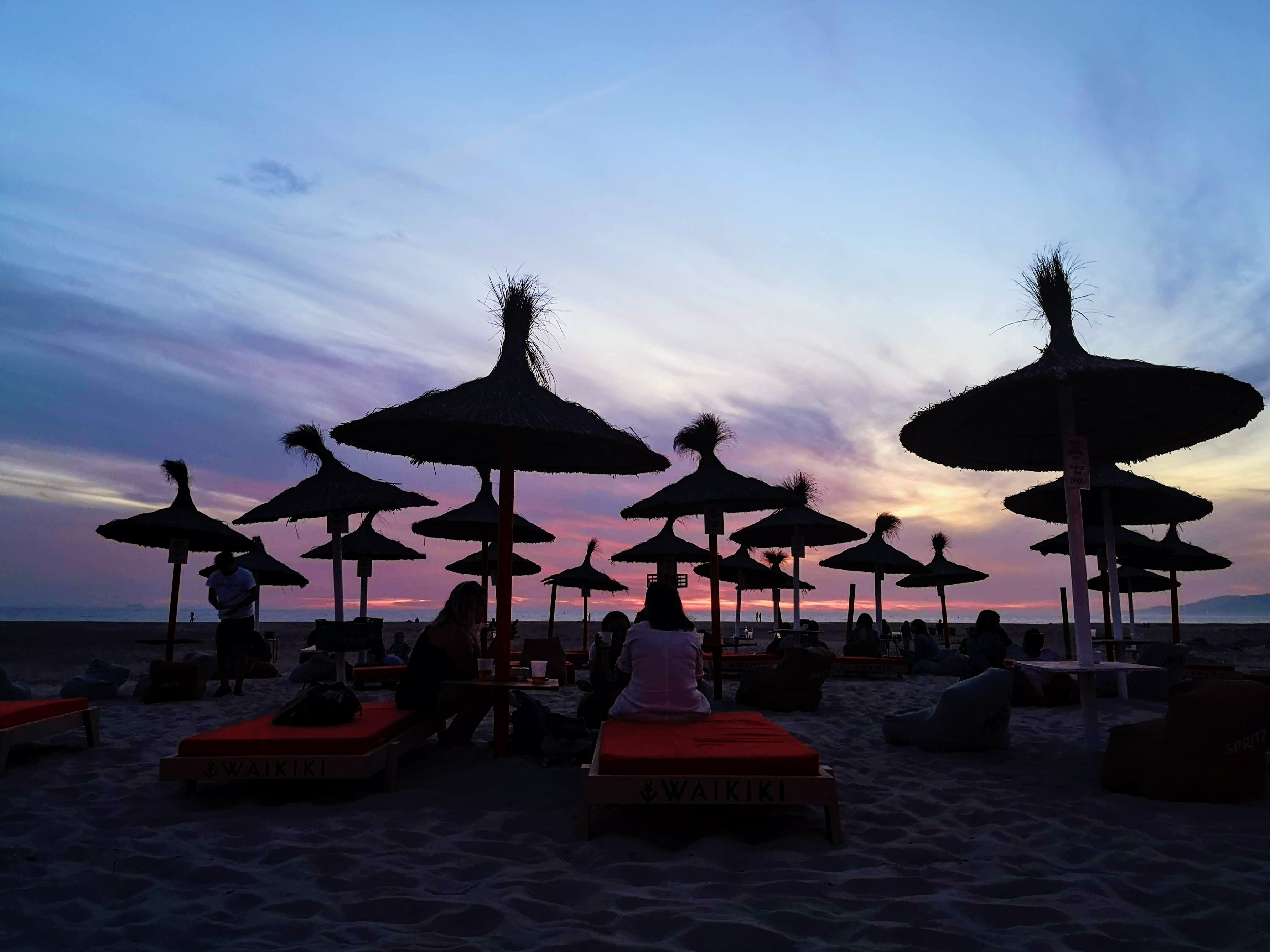 people sitting on beach chairs under umbrella during sunset