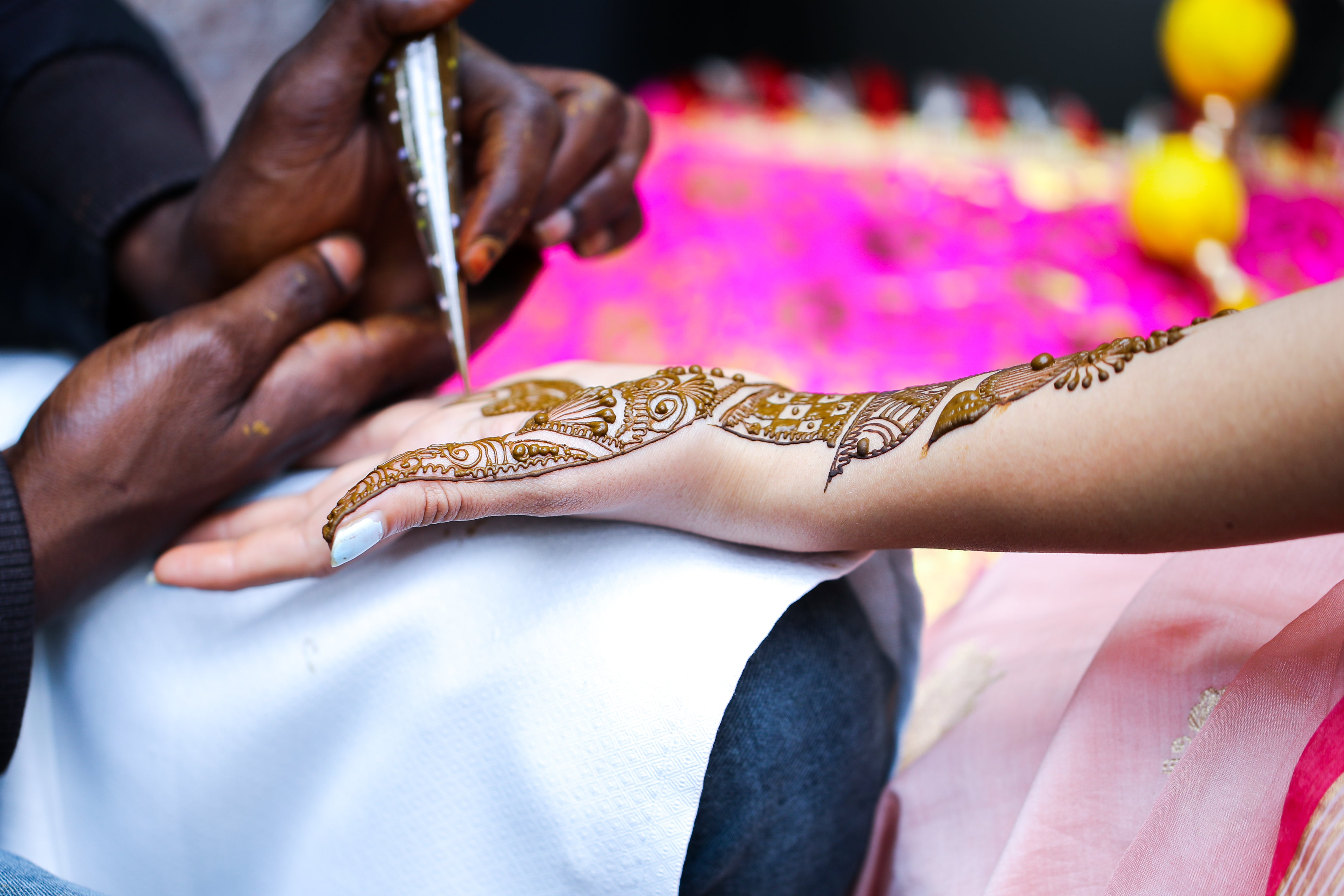 person holding pen and drawing henna on girl's hand