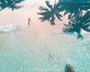 aerial view of a woman laying down on a beach