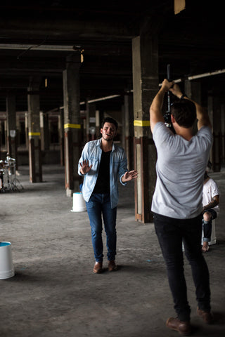 two men in a warehouse talking and taking photos