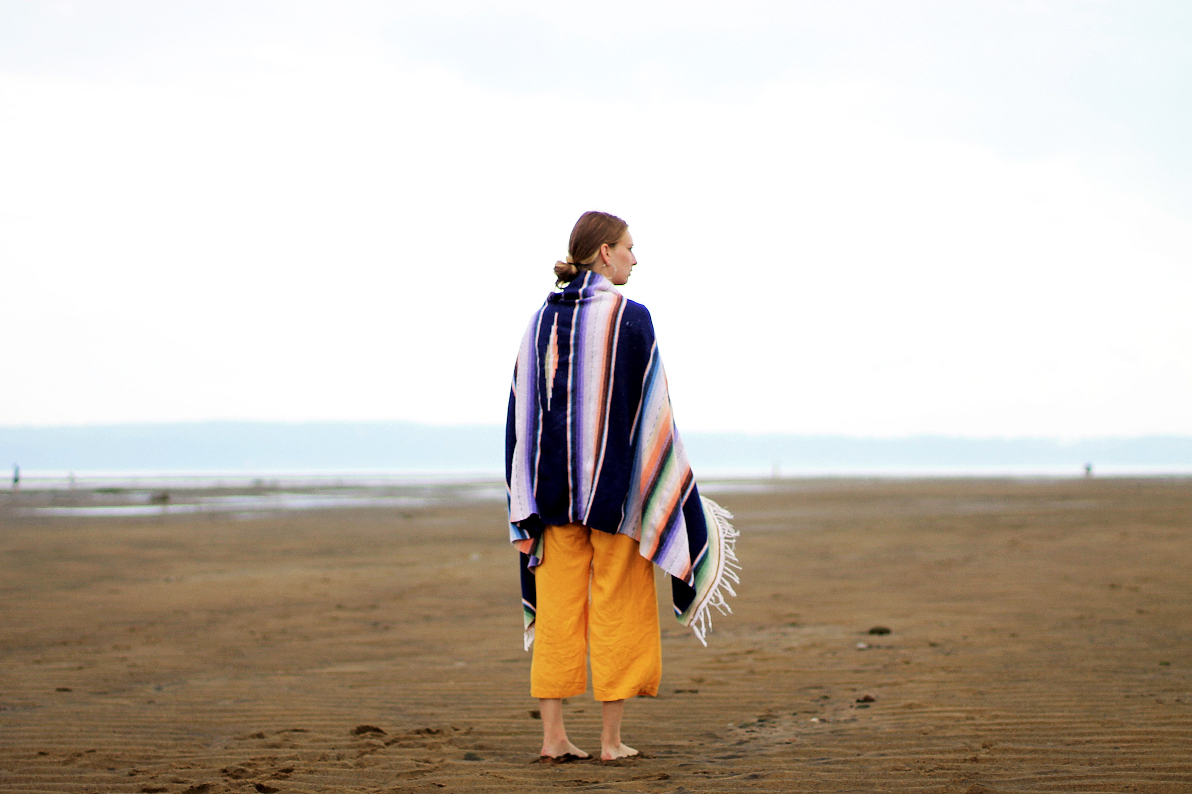 woman wearing black and white striped shoal standing on brown sand dunes