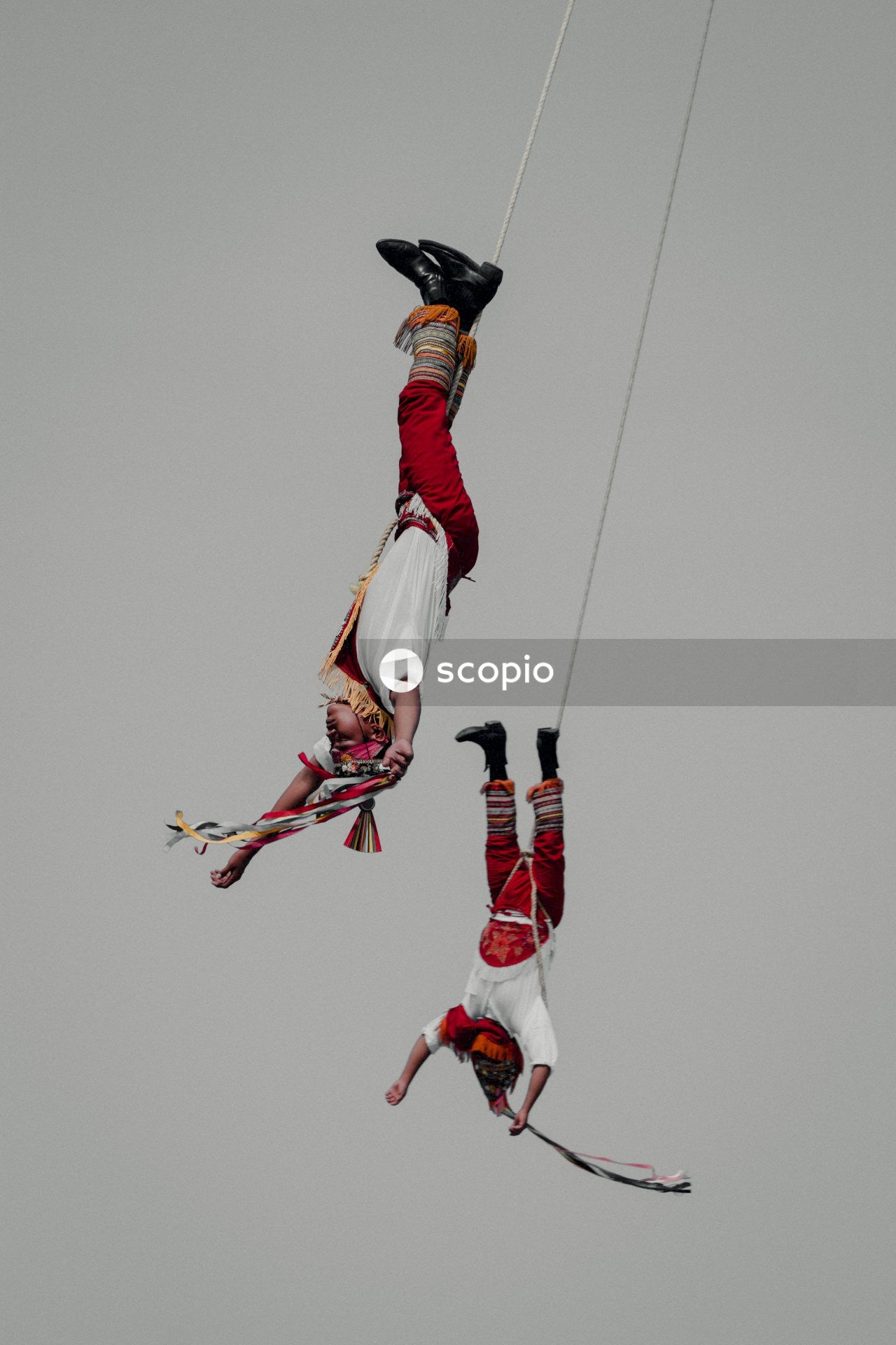 Two men hanging from rope upside down