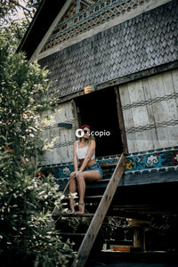Woman in blue denim shorts sitting on brown wooden bench
