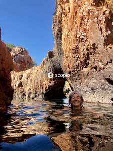 Woman in body of water near brown rock formation