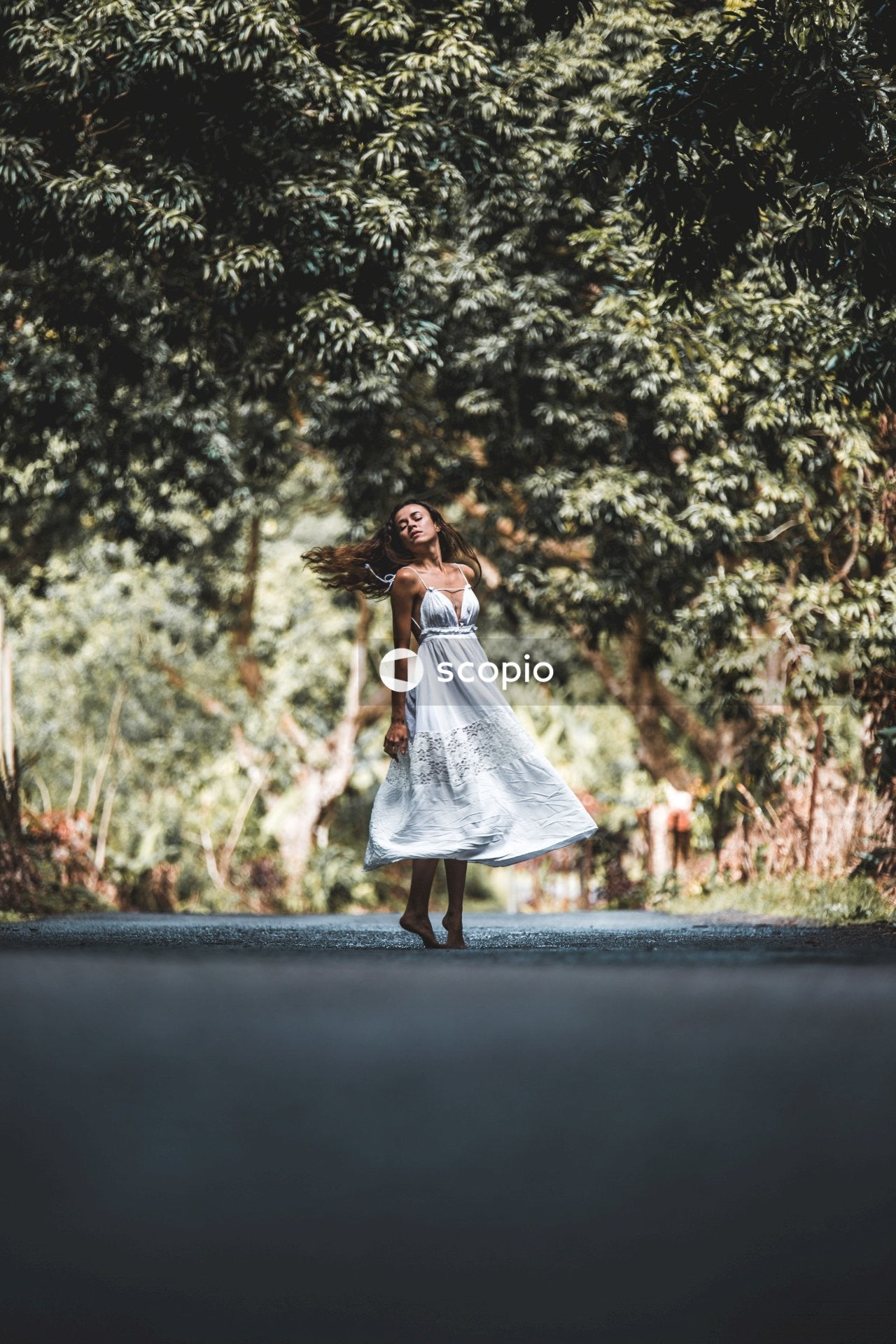 Woman in white dress standing on road