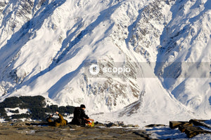 Person sitting on snow covered ground near snow covered mountain