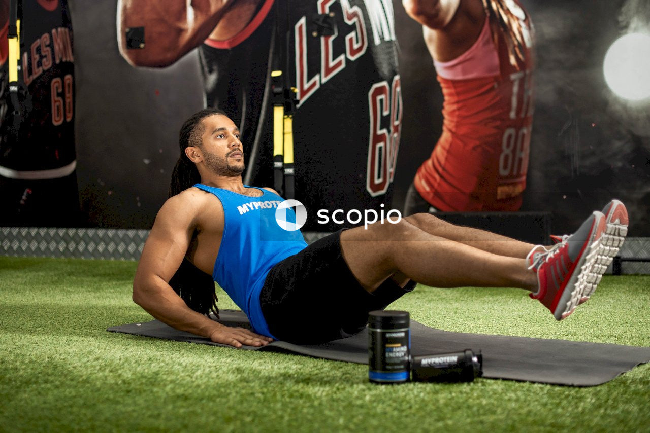 Man sitting on black yoga mat wearing blue tank top
