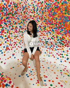 Woman in white dress shirt and white skirt sitting on multicolored wall