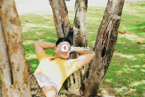 Woman in yellow shirt lying on tree