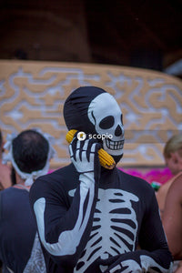Person wearing skeleton costume holding a yellow corn