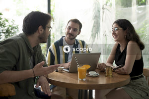 Three friends sitting at a cafe talking and working together