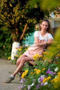 Woman sits on bench near plants