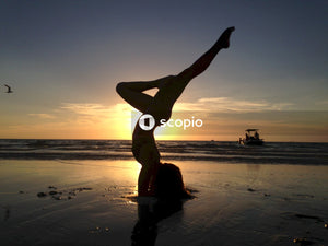 Silhouette of woman doing yoga on beach during sunset