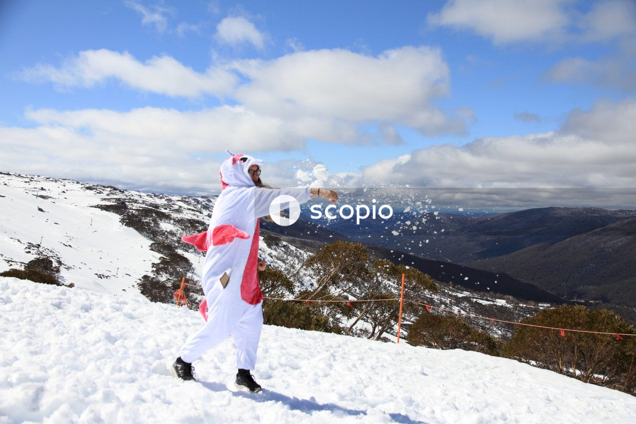 Person in white and red jacket and pants standing on snow covered ground