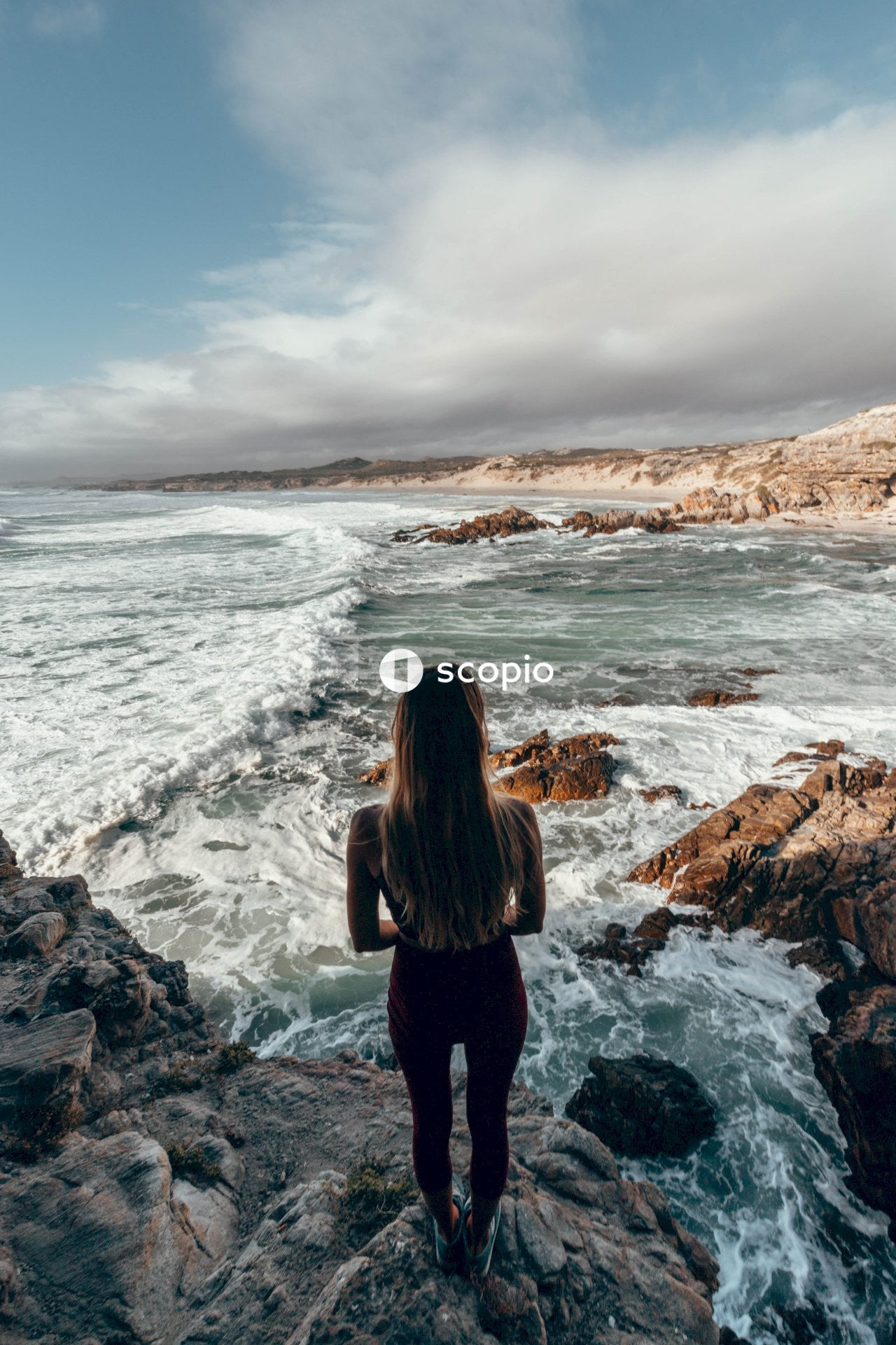 Woman standing on rock formation facing on seashore