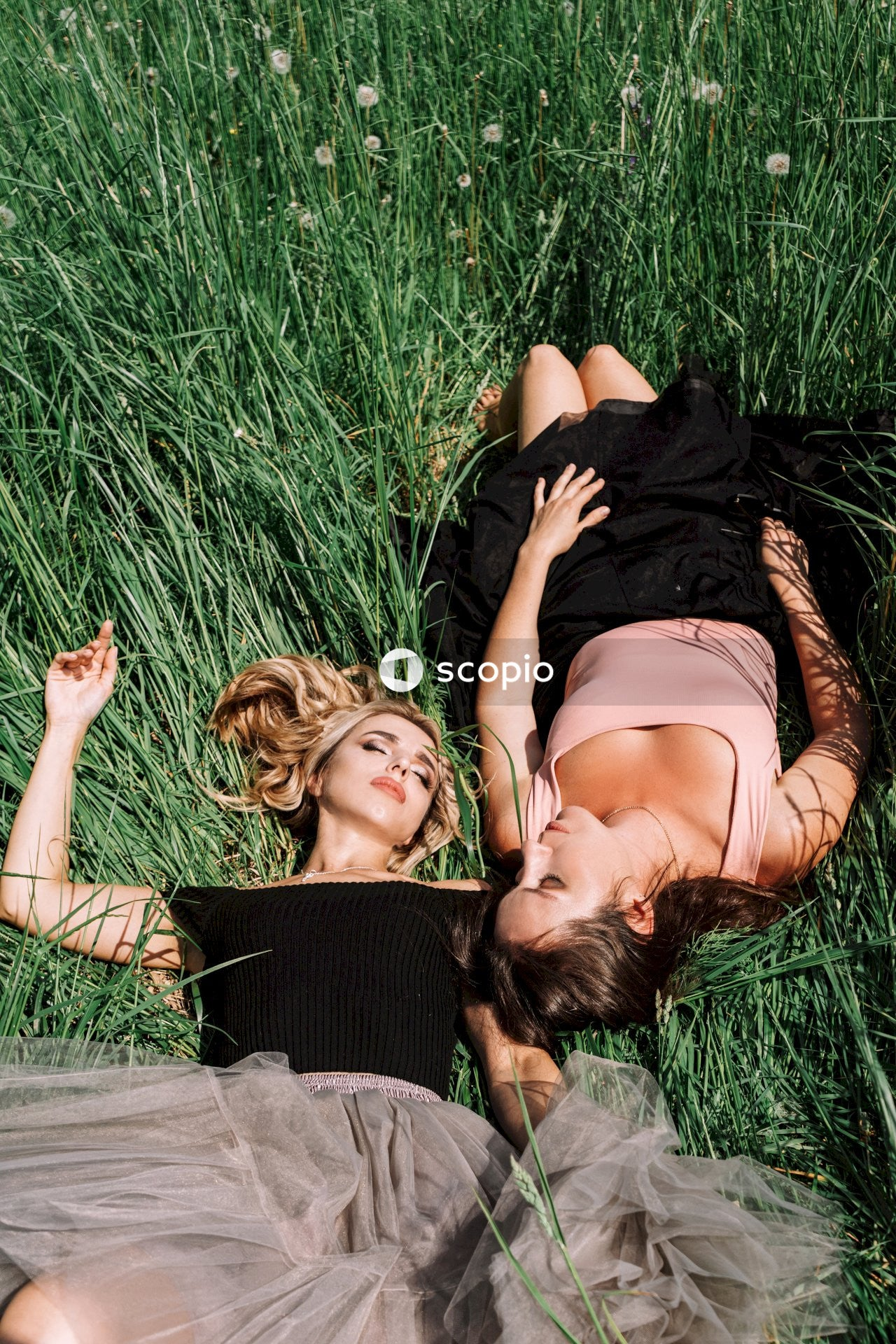 Two woman lying on the green grass field