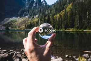 Person holding a clear sphere by calm body of water