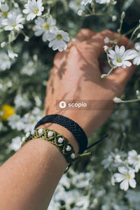 Person wearing silver and black bracelet with white flowers on left hand