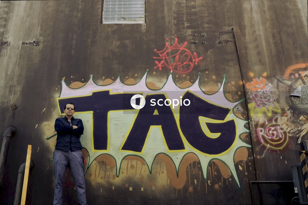 Man standing front of tag graffiti wall