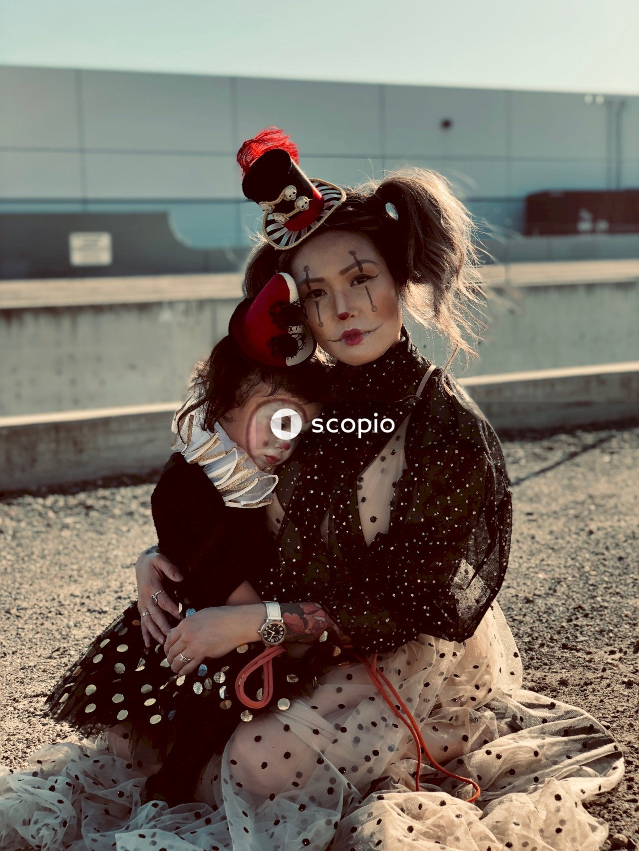 Woman and girl in clown costume sitting on brown ground