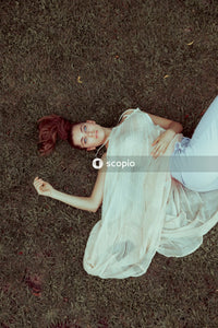 Woman in white dress lying on ground